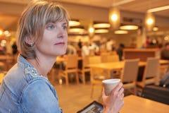 Femme s'asseyant dans le café Image libre de droits