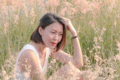 Femme s'asseyant dans le domaine d'herbe photographie stock