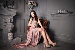 Femme s'asseyant dans le fauteuil dans la longue robe beige luxe image stock