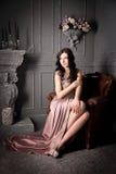Femme s'asseyant dans le fauteuil dans la longue robe beige luxe photos stock