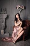 Femme s'asseyant dans le fauteuil dans la longue robe beige luxe images libres de droits