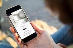 femme s'asseyant dans le site Web d'hôtel de lecture rapide de rue sur son smartp photos stock