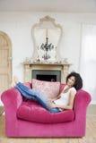 Femme s'asseyant dans le sourire de salle de séjour Photo stock