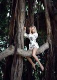 Femme s'asseyant dans les arbres énormes de jungle avec des lianes dans le tenue décontractée blanc photos libres de droits