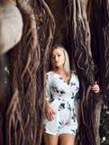 Femme s'asseyant dans les arbres énormes de jungle avec des lianes dans le tenue décontractée blanc photo libre de droits
