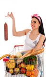 Femme s'asseyant dans un chariot à supermarché Photos stock