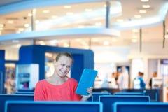 Femme s'asseyant dans un comprimé de lecture de salle d'attente Image stock