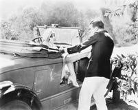 Femme s'asseyant dans un convertible donnant un coup de pied et éloignant un homme (toutes les personnes représentées ne sont pas photos libres de droits