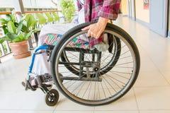 Femme s'asseyant dans un fauteuil roulant Photos stock