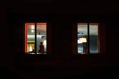 Femme s'asseyant dans une salle allumée près de la fenêtre la nuit images stock