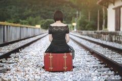 Femme s'asseyant dans une valise dans les voies de train Images stock