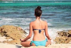femme s'asseyant de retour dans le yoga de pratique de bikini par la mer photos stock