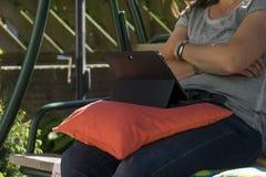 Femme s'asseyant dehors sur une banque avec ici des jambes regardant son ordinateur portable noir de comprim? Oreiller sur son re photographie stock