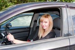 Femme s'asseyant derrière la roue d'une voiture Image libre de droits