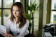 Femme s'asseyant derrière un bureau Photos libres de droits