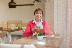 Femme s'asseyant en café Photographie stock