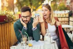 Femme s'asseyant en café avec l'homme bel et les paniers colorés Photo stock