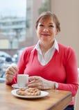 Femme s'asseyant en café avec la tasse de café Photos stock