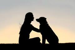 Femme s'asseyant en dehors de la silhouette de chien choyant Photographie stock
