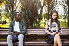 Femme s'asseyant en parc avec l'homme à l'aide du smartphone Photo stock