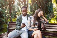 Femme s'asseyant en parc avec l'homme à l'aide du smartphone Photos libres de droits