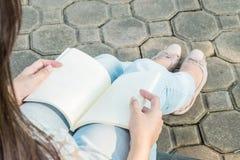 Femme s'asseyant en parc public pour lire un livre photographie stock