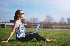 Femme s'asseyant en parc sur l'herbe verte avec l'ordinateur portable Maquette d'écran d'ordinateur étude d'herbe Copiez l'espace Photo stock