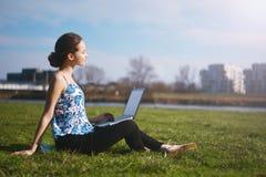 Femme s'asseyant en parc sur l'herbe verte avec l'ordinateur portable Maquette d'écran d'ordinateur étude d'herbe Copiez l'espace Images stock