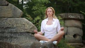 Femme s'asseyant et méditant sur le dolmen en pierre banque de vidéos