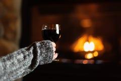 Femme s'asseyant par la cheminée de fieldstone avec le verre de vin photos stock