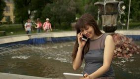 Femme s'asseyant par la fontaine avec la Tablette clips vidéos