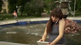 Femme s'asseyant par la fontaine avec la Tablette banque de vidéos
