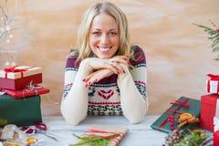 Femme s'asseyant par la table et préparant des cadeaux pour Noël Photographie stock