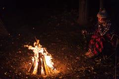Femme s'asseyant par le feu de camp la nuit avec le verre de vin image stock