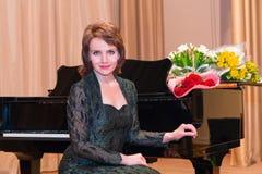 Femme s'asseyant par un piano photo stock