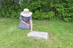 Femme s'asseyant par une tombe Photos libres de droits