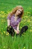 Femme s'asseyant parmi les fleurs jaunes image libre de droits