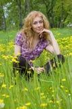 Femme s'asseyant parmi les fleurs jaunes photos libres de droits