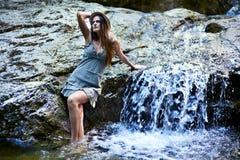 Femme s'asseyant près d'une cascade Photos libres de droits