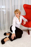 Femme s'asseyant près de la chaise rouge moderne Photographie stock libre de droits