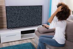 Femme s'asseyant près de la télévision sans le signal Image stock