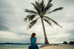 Femme s'asseyant sous le palmier sur la plage Image stock