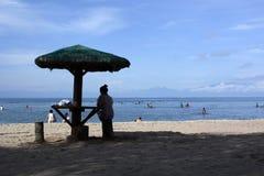 Femme s'asseyant sous le parasol sur la plage blanche de sable silhouettes Photos libres de droits