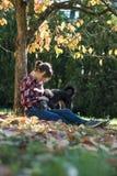 Femme s'asseyant sous un arbre caressant son chien noir Photo stock