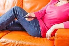 Femme s'asseyant sur des chaînes de télévision de sofa et de swith Photo libre de droits