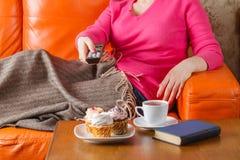 Femme s'asseyant sur des chaînes de télévision de sofa et de swith Images stock