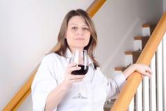 Femme s'asseyant sur des escaliers avec un verre de vin Photo stock