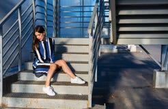 Femme s'asseyant sur des escaliers en métal Photos libres de droits