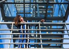 Femme s'asseyant sur des escaliers en métal Image stock