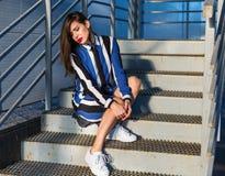 Femme s'asseyant sur des escaliers en métal Images stock
